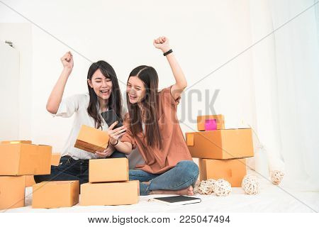 Two young Asian woman startup small business entrepreneur SME distribution warehouse with parcel mail box. Owner home office. Online marketing and product packaging and delivery service. Happy gesture