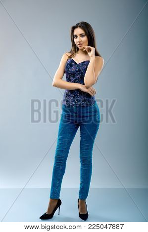 Confident and beautiful. Full length of attractive young woman in casual wear gesturing and looking at camera while standing against grey background. Model test