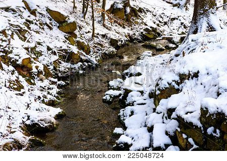 Brook from pond in snowy forest in Jevany in Winter