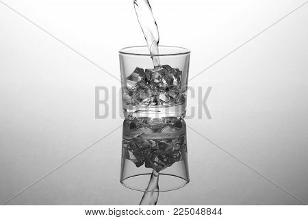 transparent glass with ice in which vodka is poured in closeup