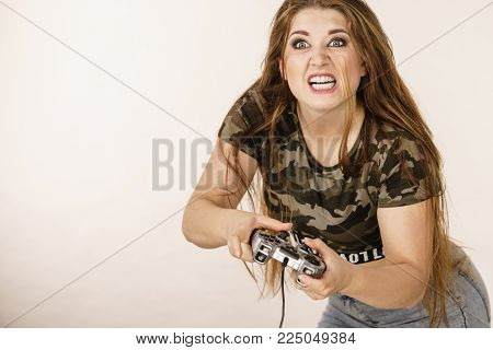 Young adult woman playing on the video console holding pad being very into game. Gaming gamers concept.
