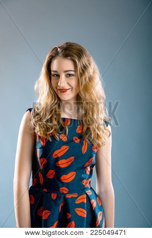 portrait of pretty young girl wearing lips printed dress and lips printed top over grey background. Model test
