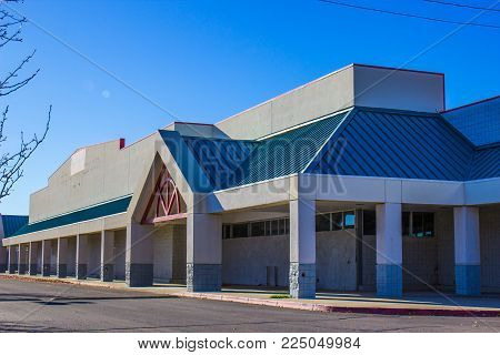 Abandoned Commercial Building With Boarded Up Entrances