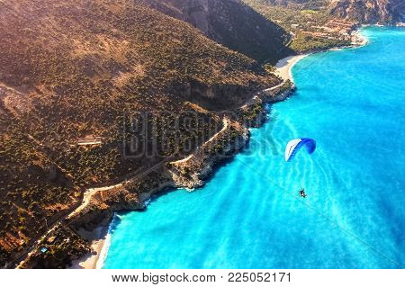Paragliding flight over the sea coast of the Mediterranean Sea. Blue parachute against the blue sea. Turkey. Oludeniz. Aerial photography. Travel and sport concept.