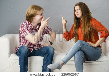 Man and woman having horrible fight while sitting on sofa. Friendship, couple breakup difficulties and problems concept.