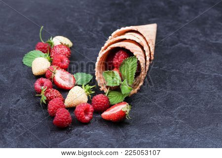 Waffle with fresh berries. Strawberries, raspberries and mint in waffle cones on a dark blue background. Copyspace. Healthy food concept