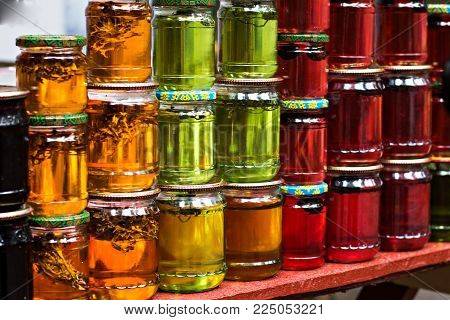 Multicolored Honey In A Jar On The Counter.