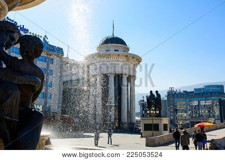 SKOPJE, MACEDONIA - OCTOBER 12, 2017: Macedonia square in Skopje city with Archeological museum and monuments shot through fountain