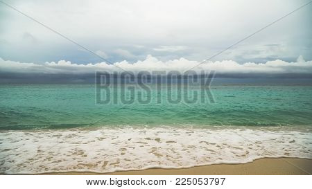 Beautiful tropical island with white sand beach and tourists in stormy weather. Puka shell beach. Tropical lagoon with turquoise water and white sand. Beautiful sky, sea, beach, resort. Beautiful tropical beach of Boracay island. Seascape: Ocean and beaut