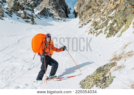 Portrait of a smiling happy freeride backcountry skier with an opened avalanche dowel abs in a backpack. Portrait on a background of a high-mountainous rocky couloir. The concept of freeride backcountry skiing and extreme winter sports