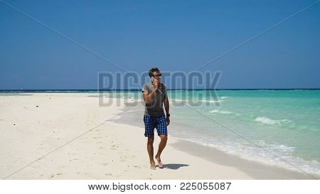 Man talking on the mobile phone at the beach. Man talking on cell phone and walking along beach. Beach, sea, sand, wave. Philippines, Travel concept.