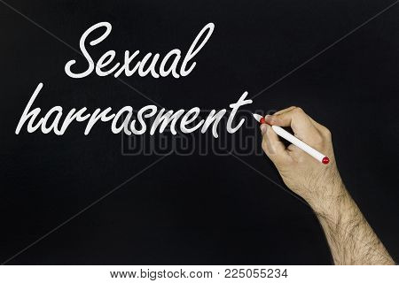 chalk drawing concept 2018. Person's hand drawing with chalk on blackboard - Sexual harassment