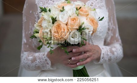 Nice wedding bouquet in bride's hand. Clip. Fiancee in a beautiful white dress holding a beautiful bouquet of wedding flowers made of tender roses in hand.