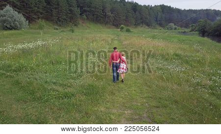 Handsome guy and blonde girl walking on the grass near the river and forest. Clip. Couple walking in the forest near the river.
