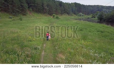 Couple walking in the forest near the river. Clip. Young family couple in love walking in the forest near the river in summer.