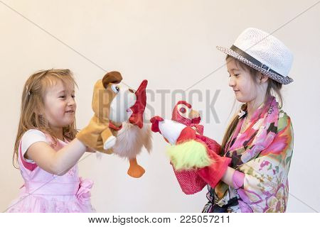 Two girls play in the puppet theater Against a light background