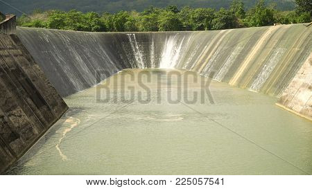 Dam on the lake in the rainforest on the island. Water flowing from the dam, Water for Irrigation countryside. Water Cascades Over Lake Bohol island, Philippines. .