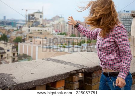 A girl in a plaid shirt and blue jeans makes a movement with her hand as if she were throwing something away. against the background of the cityscape.