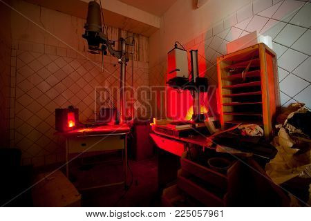 Vintage photo lab, with enlargers and other equipment, with red light for photographic film development.