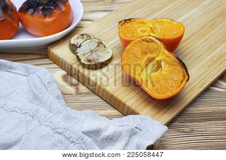 A photo of the sliced antioxidant grilled mandarine fruits and limes on the wooden table. Food for longevity, long life. New Japanese superfood, grilled tangerines. New convincing eastern superfoods