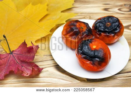 New Japanese superfood, grilled tangerines with the peel. A photo of the antioxidant grilled mandarines on the plate for longevity, long life. New convincing superfoods. Autumn yellow maple leaves