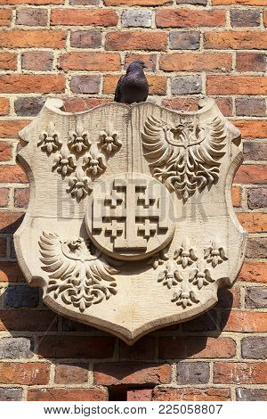 13th century Gothic Collegiate Church of the Holy Cross and St. Bartholomew, relief on facade, Ostrow Tumski, Wroclaw, Poland.  It is a two-storey brick church on the Cathedral Island