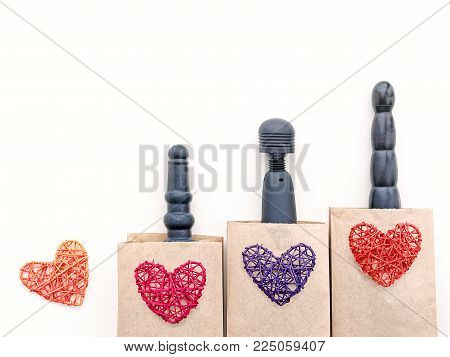 Various sex toys (dildos and wand-massager) are in paper bags. On top of them are figures of wicker hearts. The idea to buy gifts for adults in a sex store on Valentine's Day.