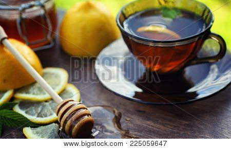 Tea with lemon and mint in nature. A cup of hot mint tea with lemon and honey in jar. Lemon slices and a spoon with honey to hot tea.
