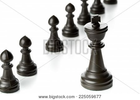 King chess figure in front of row of pawn chess figures - management, leadership, teamlead or strategy concept over white background