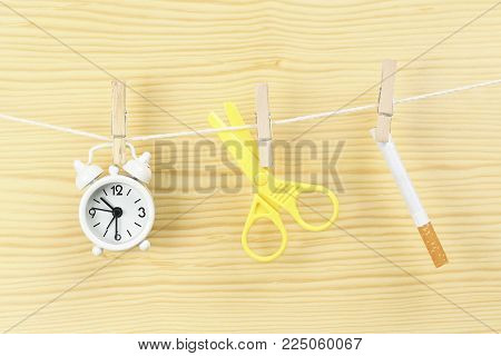 time to quit smoking concept with clock, scissors and cigarette on clothesline