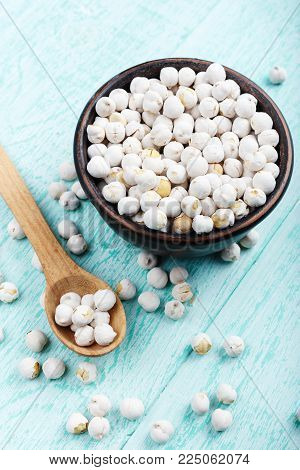 raw chickpeas in a plate on a wooden background, organic food, vegetarian cuisine