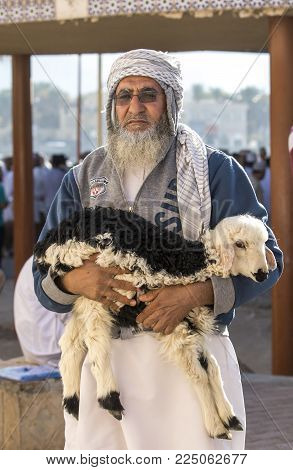 Nizwa, Oman, Febrary 2nd, 2018: Old Man Waling Away From A Market With A Baby Sheep
