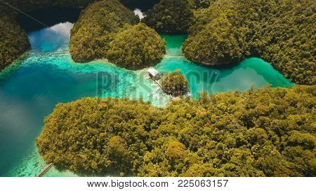 Aerial view: beach, tropical island, sea bay and lagoon, Siargao. Tropical landscape hill, clouds and mountains rocks with rainforest. Azure water of lagoon. Shore Landscape Bay. Travel concept.