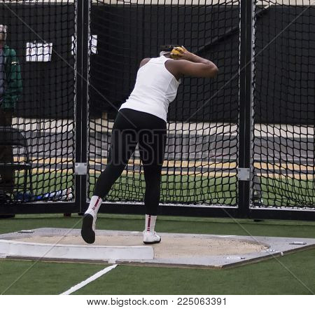 An African American high school girl is set up in the throwing circle to throw the shot put in a competition.