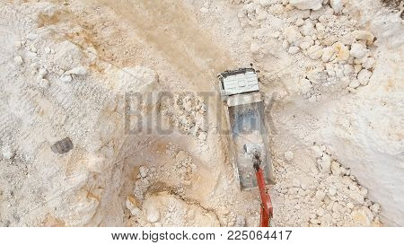 Excavator loads the truck in a limestone quarry. Aerial view wheel loader excavator machine loading dumper truck at quarry. Earth mover loading dumper truck with rocks in quarry. Philippines. Travel concept.