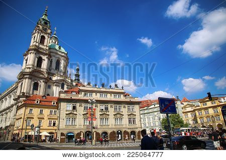 PRAGUE, CZECH REPUBLIC - AUGUST 24, 2016: People walking and look around Malostranske namesti and view of Cathedral of Saint Nicolas ( in Mala Strana district) in Prague, Czech Republic