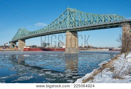 Montreal Jacques Cartier Bridge in winter, with chunks of ice floating on the Saint-lawrence (2018)