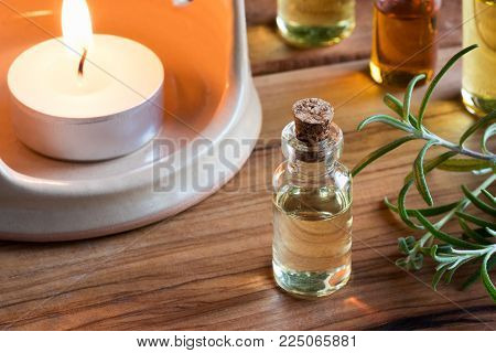 A bottle of rosemary essential oil with fresh rosemary twigs and a candle