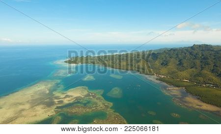 Aerial view: beach, tropical island, sea bay and lagoon, Bohol. Tropical landscape hill, clouds and mountains rocks with rainforest. Azure water of lagoon. Shore Landscape Bay. Aerial video.Seascape. Travel concept.