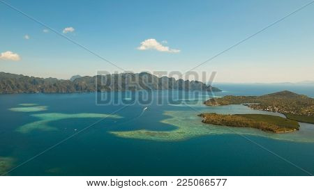 Aerial view: beach, tropical island, sea bay and lagoon, mountains with rainforest, Busuanga, Palawan. Seascape, tropical landscape Azure water of lagoon Philippines