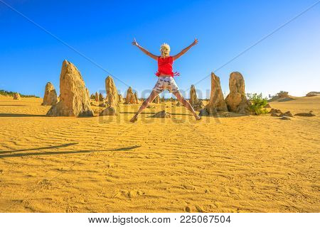 Western Australia travel freedom concept. Happy caucasian woman jumping at Pinnacles Desert, Nambung National Park, Cervantes. Female lifestyle traveler enjoying limestone formations in Australia.