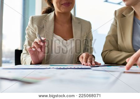 Close-up shot of unrecognizable team of financial managers discussing statistic data while having working meeting in modern boardroom