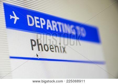 Computer screen close-up of status of flight departing to Phoenix, Arizona, USA