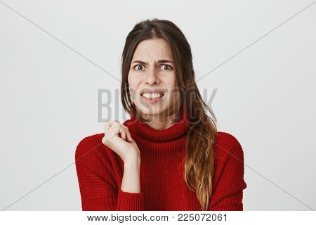 Body language. Disgusted stressed out pretty girl with ponytail in red sweater posing against studio wall, frowning her face, clenching her white teeth, demonstrating aversion to something