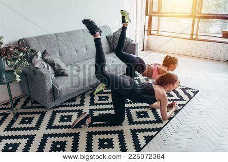 Two sportive female friends doing butt toning exercise performing donkey kicks at home.