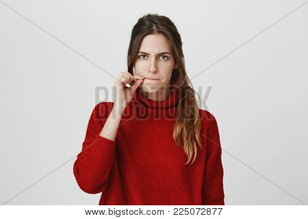 Studio shot of beautiful young woman in red sweater closing her mouth, seriously looking at camera, asking to keep her secret, not to tell anyone. Confidential information concept.