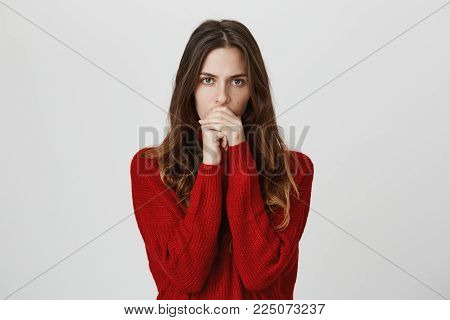 Studio shot of serious pensive young female with long hair dressed in red sweater closing her mouth, having concentrated puzzled look, thinking about serious life decision. Human emotions, feelings and face expression