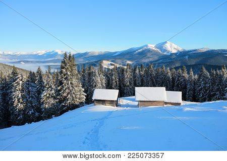 A trodden path leads to the wooden house in the snow on the background of beautiful snow-capped mountains. Winter landscape for leaflets.
