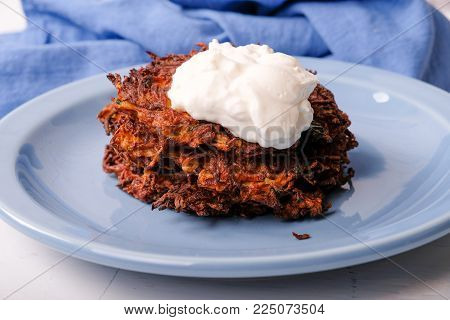 zucchini and carrot latkes or pancakes, with sour cream, a ketogenic diet meal
