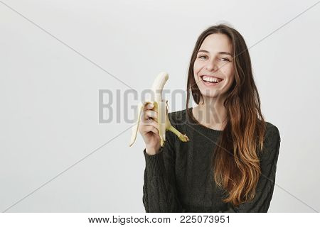 Portrait of young gorgeous brunette model smiling sincerely, holding banana over white background. Healthy lifestyle and body positive concept. Fruit will give energy for the whole morning.